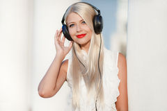 Jeune femme avec des écouteurs Appréciez la musique Images stock