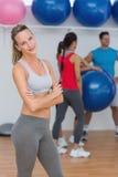 Jeune femme avec des amis à l'arrière-plan au studio de forme physique Photographie stock libre de droits