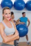 Jeune femme avec des amis à l'arrière-plan au studio de forme physique Image libre de droits