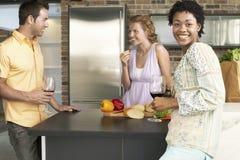 Jeune femme avec des amis au comptoir de cuisine Image libre de droits