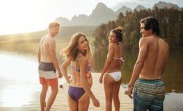 Jeune femme avec des amis et marche sur la jetée Image stock