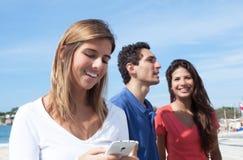 Jeune femme avec des amis introduisant un message au téléphone Photographie stock libre de droits