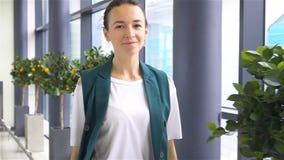 Jeune femme avec des bagages dans l'aéroport international marchant avec son bagage Passager de ligne aérienne dans un salon d'aé banque de vidéos