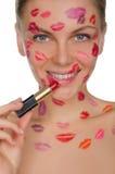 Jeune femme avec des baisers sur le visage dans le rouge à lèvres et des lèvres Photo libre de droits