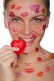 Jeune femme avec des baisers sur le visage tenant le coeur dans la bouche Photos stock
