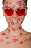 Jeune femme avec des baisers sur son visage et verres, coeurs Image stock