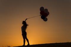 Jeune femme avec des ballons au coucher du soleil Photos stock