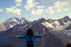 Jeune femme avec des bras tendus dans les montagnes Le concept du bonheur, liberté, plaisir Photographie stock