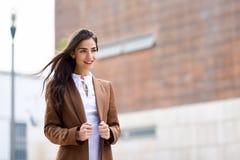 Jeune femme avec des cheveux dans le vent à l'arrière-plan urbain Images stock