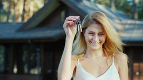 Jeune femme avec des clés de maison Sourire, regardant l'appareil-photo Nouveau cottage en bois à l'arrière-plan Photo libre de droits