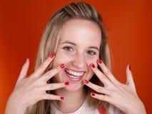 Jeune femme avec des doigts au-dessus de son visage Photo stock