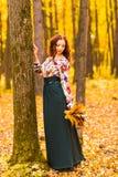 Jeune femme avec des feuilles d'automne à disposition Photo stock