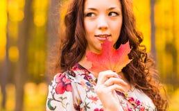 Jeune femme avec des feuilles d'automne à disposition Photos libres de droits