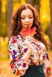 Jeune femme avec des feuilles d'automne à disposition Images libres de droits
