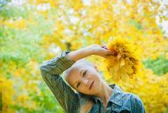 Jeune femme avec des feuilles d'automne photos stock