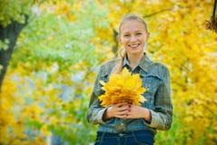 Jeune femme avec des feuilles d'automne photographie stock libre de droits