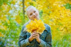 Jeune femme avec des feuilles d'automne images stock