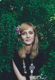 Jeune femme avec des fleurs dans ses cheveux regardant l'appareil-photo Photos stock