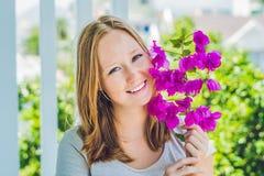 Jeune femme avec des fleurs de pourpre de ressort contre les jeunes jaunes blancs de source de fleur de concept de fond images stock
