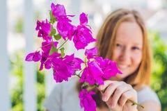 Jeune femme avec des fleurs de pourpre de ressort contre les jeunes jaunes blancs de source de fleur de concept de fond Photographie stock
