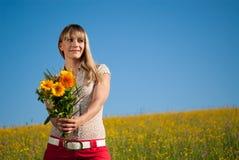 Jeune femme avec des fleurs pour le jour de mère Image libre de droits