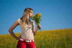 Jeune femme avec des fleurs pour le jour de mère Images stock