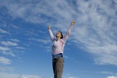 Jeune femme avec des mains dans le ciel Images stock