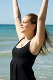 Jeune femme avec des mains exprimant vers le haut la joie sur la côte Images libres de droits
