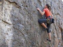 Jeune femme avec des montées de corde sur la roche Image stock