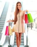 Jeune femme avec des paniers dans le centre commercial Photo stock