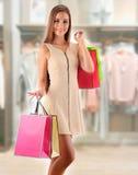 Jeune femme avec des paniers dans le centre commercial Images stock