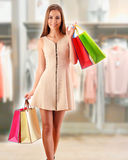 Jeune femme avec des paniers dans le centre commercial Image libre de droits