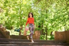 Jeune femme avec des paniers descendant les escaliers dehors Photographie stock