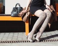 Jeune femme avec des paniers se reposant près de la boutique Photo libre de droits