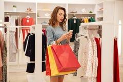 Jeune femme avec des paquets utilisant le smartphone Image libre de droits