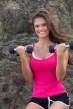 Jeune femme avec des poids de mains par formation de roche Photographie stock libre de droits