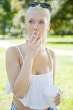 Jeune femme avec des questions de fumée en parc Photos libres de droits