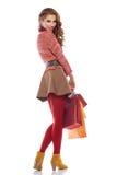 Jeune femme avec des sacs à provisions au-dessus de blanc photographie stock