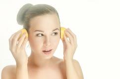 Jeune femme avec deux moitiés d'un citron photographie stock