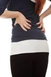 Jeune femme avec douleur dans elle en arrière. Photo libre de droits