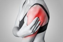 Jeune femme avec douleur sur son bras et épaule sur le fond gris Images stock
