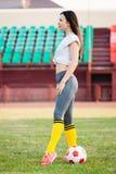 Jeune femme avec du ballon de football au stade photographie stock libre de droits