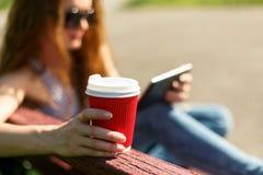 Jeune femme avec du café à aller marquer sur tablette le PC sur un banc Photos stock