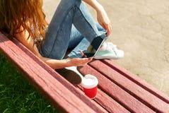 Jeune femme avec du café à aller marquer sur tablette le PC sur un banc Photographie stock