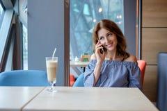 Jeune femme avec du charme appelant avec le téléphone de cellules tout en seul se reposant dans le café, femelle attirante avec l image stock