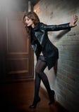 Jeune femme avec du charme de brune dans le manteau en cuir au-dessus des bas noirs posant près du mur de briques rouges Jeune fe Image stock