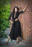 Jeune femme avec du charme de brune dans le noir et talons hauts restant près d'un mur de briques rouge Photos stock