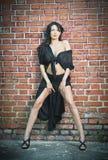 Jeune femme avec du charme de brune dans le noir et talons hauts restant près d'un mur de briques rouge Images libres de droits