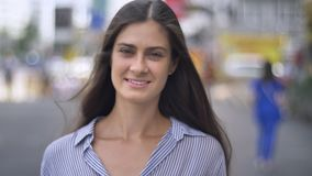 Jeune femme avec du charme entrant dans le foyer, marchant sur la rue urbaine, belle femelle de brune avec de longs cheveux banque de vidéos