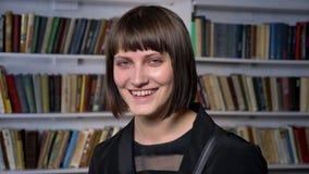 Jeune femme avec du charme heureuse avec la coupe de cheveux courte se tenant dans la bibliothèque et souriant à l'appareil-photo clips vidéos